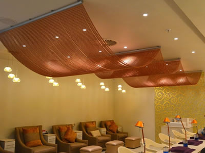 Red chain link curtain is fixed on the ceiling to decorate the room, and there is a lot of chairs, sofas and table with small lamps.