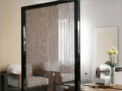 Black chain link curtain as screen to decorate the room, and there are two sofas, one table in it.