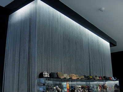 Silver Chain Link Curtain As Background For Showcase And Model Toys In The