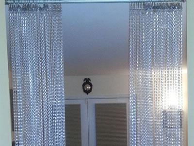 Chain link curtain in silver color hangs on two sides of the wall, like a door.