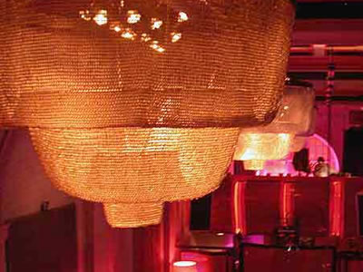Chainmail curtain decorates ceiling lamp that reflects a soft lighting.