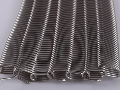 Details about dense wire mesh belt and its edge, it is lying on the white background.