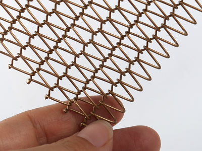 A piece of copper fine round wire mesh belt is held by one's hand.