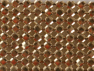 Quincunx shape scale mesh curtain sample in golden color is lying on the background.