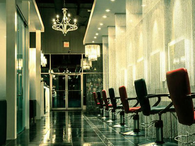 Metal bead curtain decorates barber shop, there are chairs and mirrors in it.