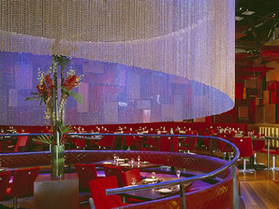 Metal bead curtain is hanging on the ceiling to decorate the nightclub, under it is several chairs, tables and tableware.
