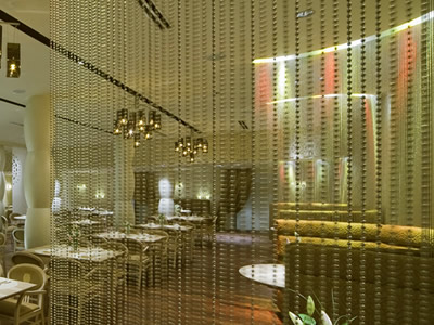 Metal bead curtain decorates restaurant, and there are sofas, white table and a pot plant in it.
