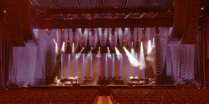 Metal bead curtain decorates the stage with a good drooping, and there is a piano, group drums on it, and thousands of chairs below the stage.