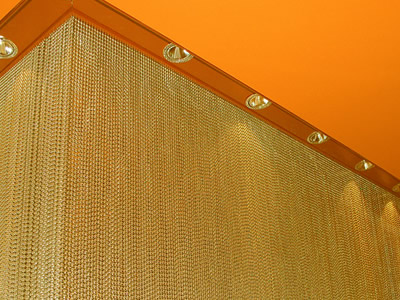 Metal bead curtain is hanging on the orange ceiling and used as wall decoration.