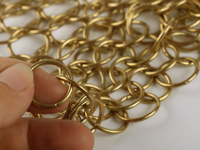 No welded single ring of chainmail curtain in golden color.