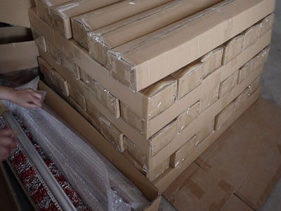 Many packaged cartons pile up together on the ground, and two packaging cartons beside them.