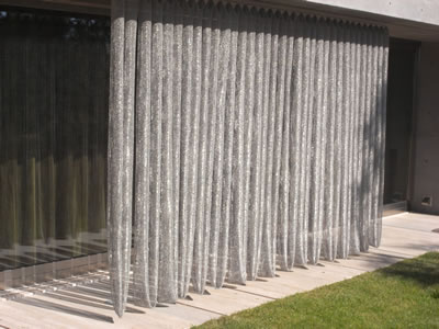 A silver scale mesh curtain is hanging outside to resist sunshine and dividing the house from grassland.