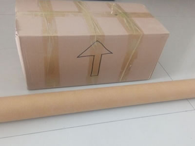 A packaged carton and a chain curtain roll with water proof paper on the ground.