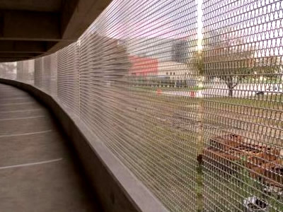 Wire mesh belt as wall cladding material ensure the security, and outside of it is grass land, houses and road.