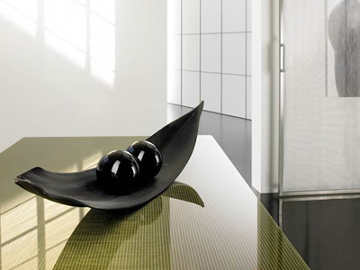 Wired glass as a table, and there is a black decorative metal leaf with two black balls on it.
