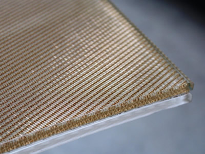 A part of wired glass laminated with woven wire mesh edge.