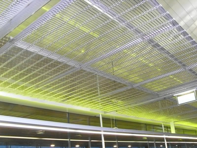 Woven wire drapery in metallic color decorates ceiling in public area.